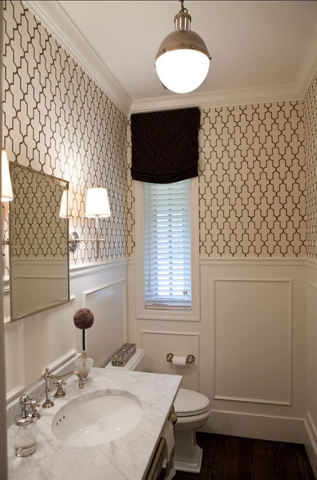 A Moroccan inspired grasscloth from Phillip Jeffries and white wainscoting give a fresh look to the powder room